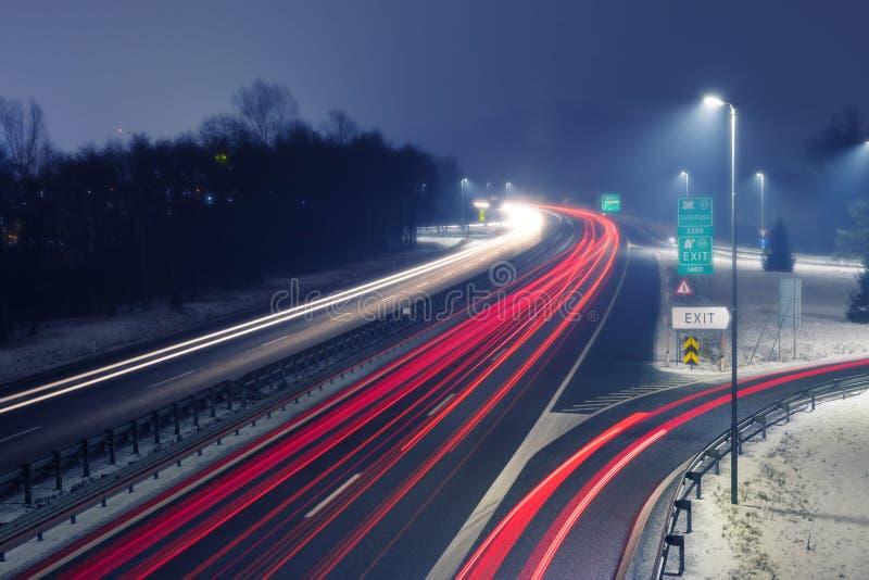 Weg bij nacht met heldere slepen van licht van inkomend en uitgaand verkeer stock afbeeldingen