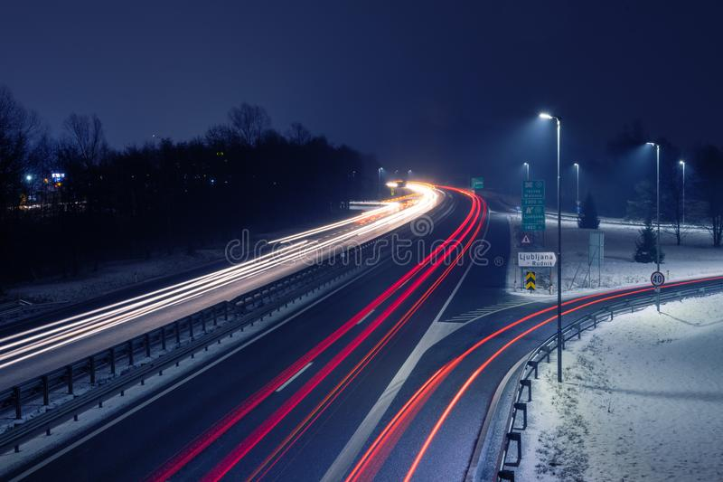Weg bij sneeuwnacht met slepen van licht van inkomend en uitgaand verkeer royalty-vrije stock afbeeldingen