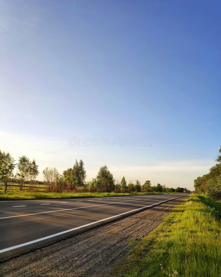 Weg in de lente en blauwe duidelijke hemel stock afbeeldingen