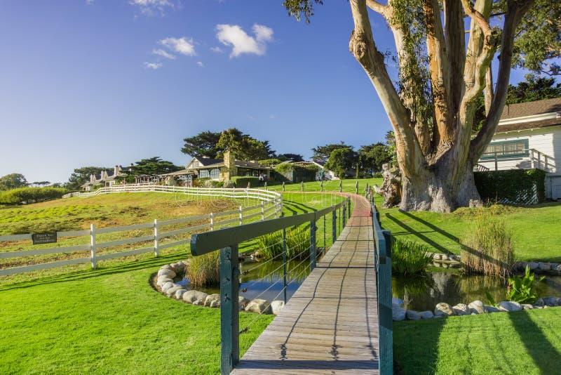 Weg, der über eine grüne Wiese hinausgeht; Restaurants im Hintergrund, Halbinsel des Carmel-durch-d-Meer, Monterey, Kalifornien lizenzfreies stockfoto