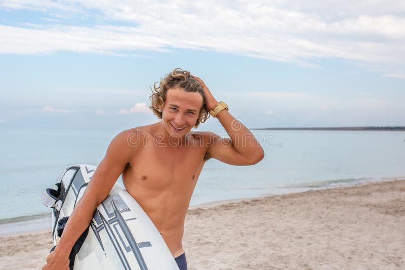 Weg des gutaussehenden Mannes mit weißem leerem Wartung des surfenden Brettes die Welle, zum der Stelle am Seeozeanufer zu surfen stockbild