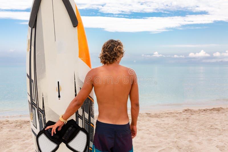 Weg des gutaussehenden Mannes mit weißem leerem Wartung des surfenden Brettes die Welle, zum der Stelle am Seeozeanufer zu surfen stockfotografie