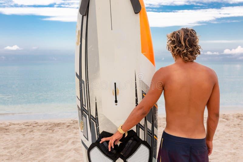 Weg des gutaussehenden Mannes mit weißem leerem Wartung des surfenden Brettes die Welle, zum der Stelle am Seeozeanufer zu surfen stockfoto