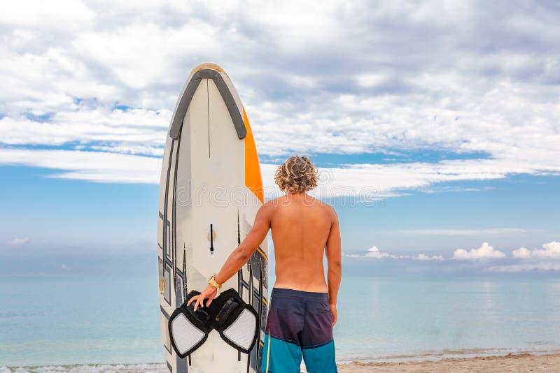 Weg des gutaussehenden Mannes mit weißem leerem Wartung des surfenden Brettes die Welle, zum der Stelle am Seeozeanufer zu surfen lizenzfreies stockfoto