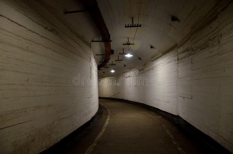 Weg door een donkere gebogen overspannen tunnel met lichte muren in een oud verlaten gebouw stock foto's