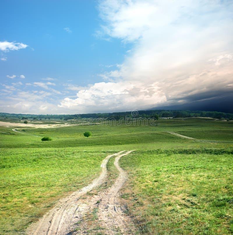 Weg en onweerswolken stock afbeelding