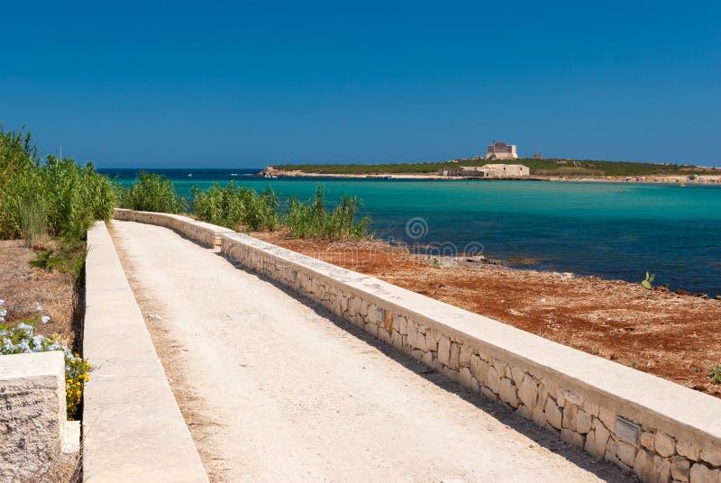 Weg langs de kustlijn in Portopalo zuidelijk Sicilië; het eiland van ` Capo Passero ` op de achtergrond stock afbeelding