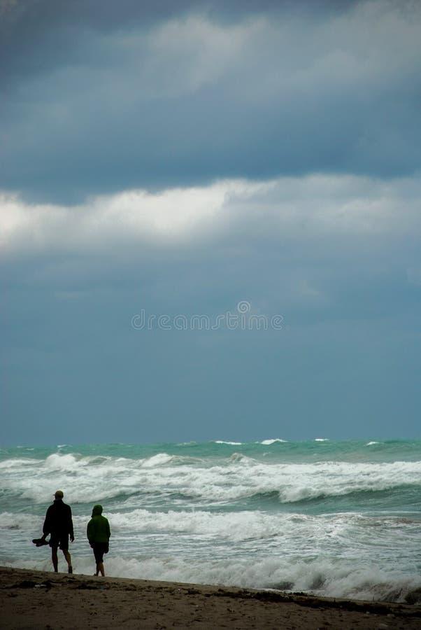 Weg mit zwei Leuten auf dem Strand bei schlechtem Wetter stockfoto