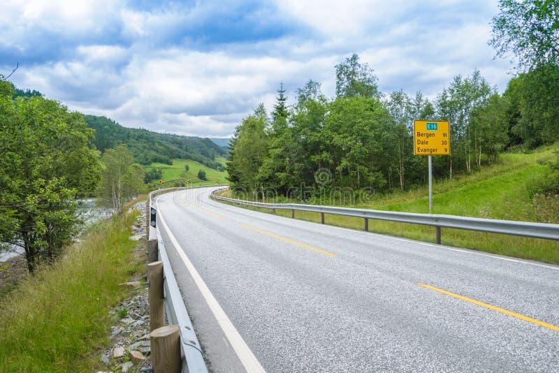 Weg in Noorwegen langs het bos en de rivier stock foto