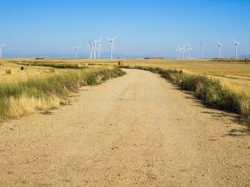 Weg onder graangewassengebieden en windturbines royalty-vrije stock afbeeldingen