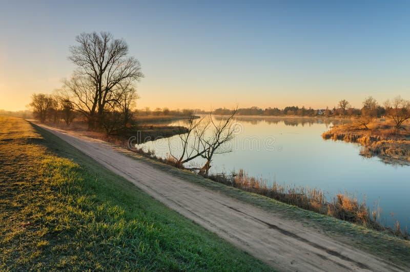 Weg op de kust van een wilde vijver naast een dorp tijdens zonsopgang in de herfstochtend stock foto's