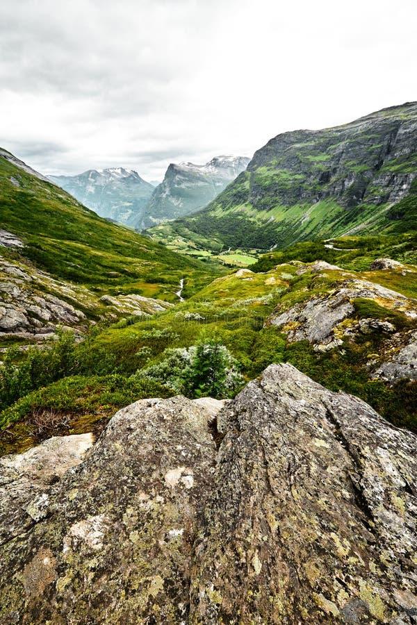 Weg over groen weiland in de bergen van Westelijk Noorwegen met sneeuw op de toppen en een donkere bewolkte hemel stock foto