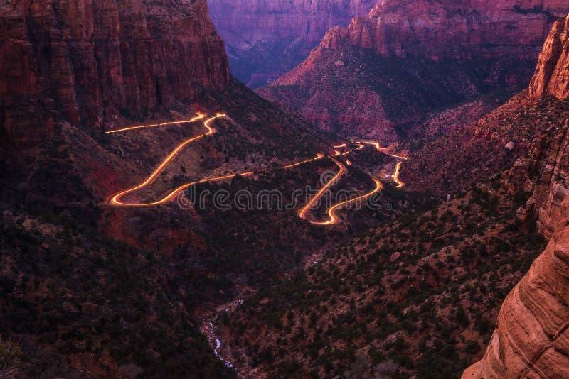 Weg in Zion National Park met auto lichte slepen stock afbeeldingen
