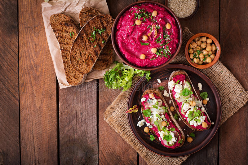 Weganin ściska z beetroot hummus, ogórkiem i błękitnym serem, zdjęcia stock