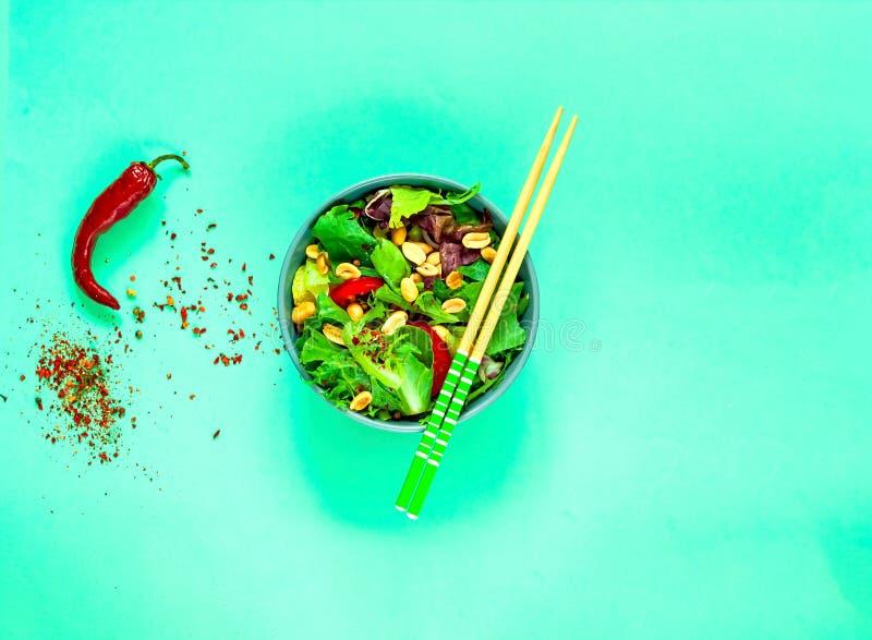 Weganin Jarzynowa sałatka z arachidami w błękitnym pucharze z chopsticks na zielonym tle Organic Jedzenia pojęcie obraz royalty free