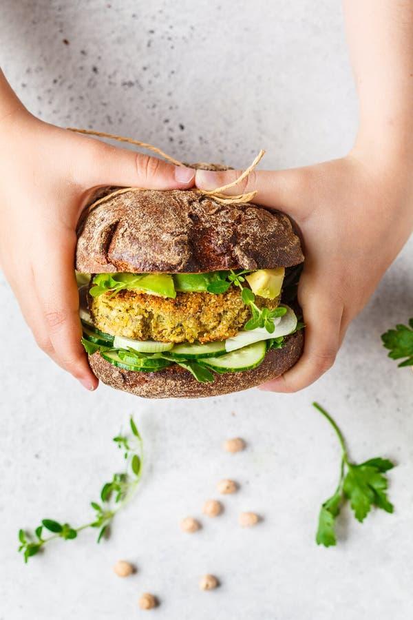 Weganin kanapka z pasztecikiem, avocado, og?rkiem i zieleniami w ?yto chlebie w dziecko r?kach chickpea, zdjęcia royalty free