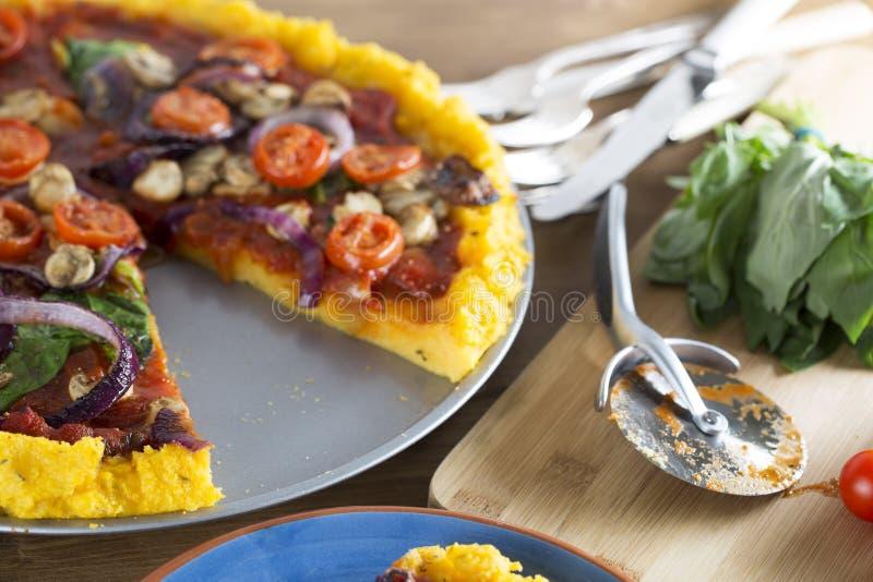 Weganin polenty pizza z plasterka chybianiem zdjęcie stock