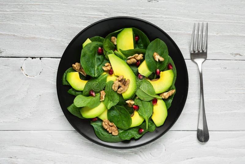 Weganin sałatka z avocado, szpinakiem, granatowem i orzechami włoskimi w czarnym talerzu z rozwidleniem, zdrowa żywność obraz stock