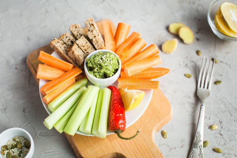 Weganin zdrowe przekąski: guacamole, marchewki, seler zdjęcie royalty free