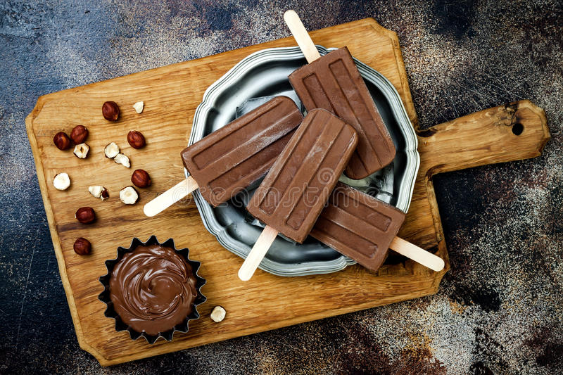 Weganinu czekoladowego fudge bananowi popsicles z domowej roboty hazelnut rozszerzaniem się Śmietankowego nabiału bezpłatni lodow zdjęcie royalty free