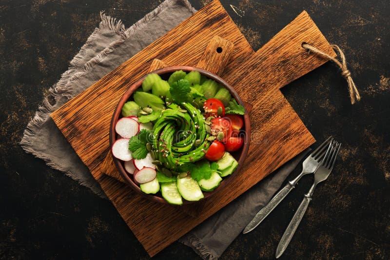 Weganinu jedzenie Zdrowa sałatka z świeżymi warzywami, avocado, rzodkiew, pomidor, ogórek, seler, ziarna na ciemnym tle Odgórny w obraz stock