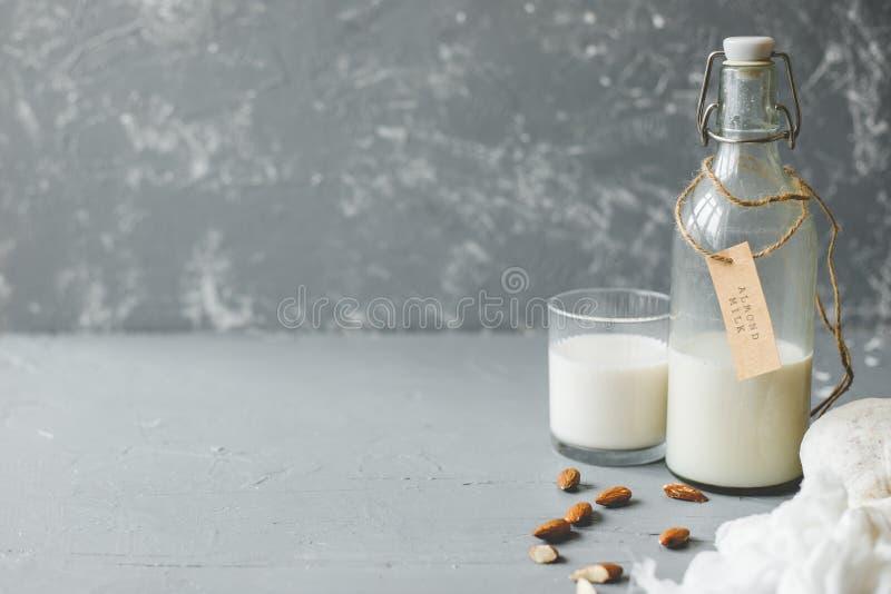 Weganinu migdału mleko w szklanej butelce z migdałami na drewnianym tle z kopii przestrzenią zdjęcie royalty free