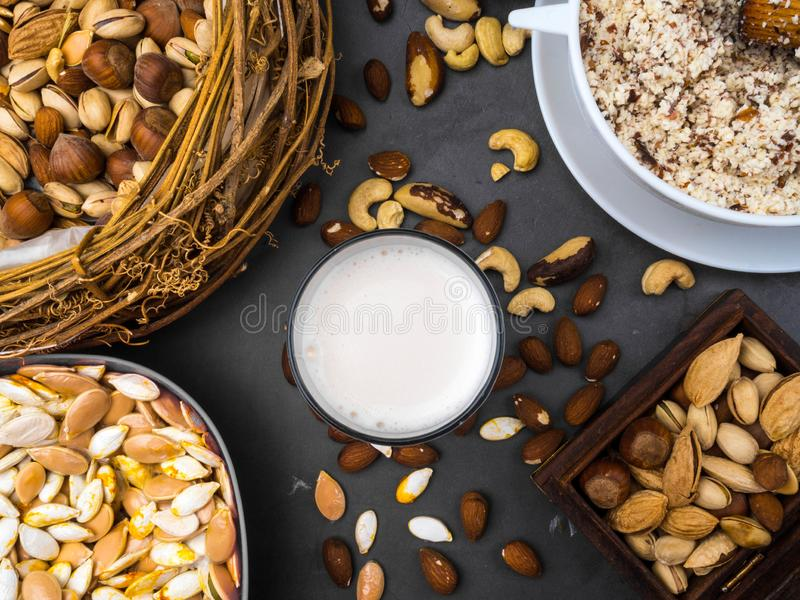 Weganinu mleko od dokrętek w szkle z różnorodnymi dokrętkami Organicznie zdrowy przekąska weganinu jarosz obraz royalty free