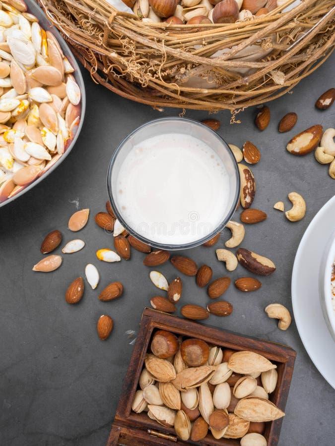 Weganinu mleko od dokrętek w szkle z różnorodnymi dokrętkami Organicznie zdrowy przekąska weganinu jarosz zdjęcia stock