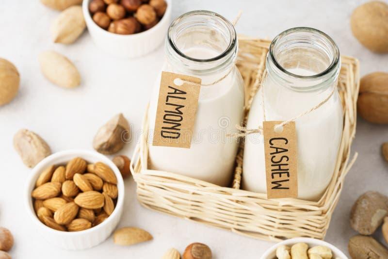 Weganinu mleko robić dokrętki w szklanych butelkach - migdał i nerkodrzew zdjęcie royalty free