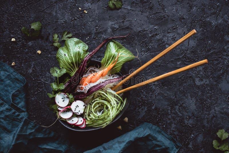 Weganinu puchar z chopsticks Azjatycka sałatka z ryżowymi kluskami, marchewką, rzodkwią i ogórkiem na czarnym tle, Odgórny widok fotografia stock
