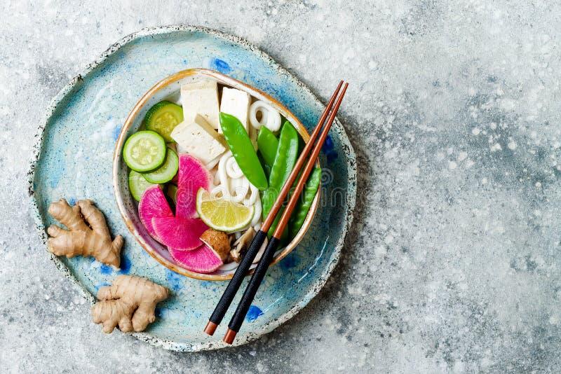 Weganinu udon klusek azjatykci zupny puchar z imbirem i pieczarkami rosół, tofu, nagli grochy, zucchini, arbuz rzodkiew i wapno, zdjęcia stock