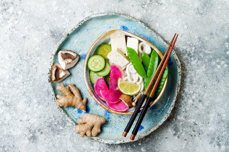 Weganinu udon klusek azjatykci zupny puchar z imbirem i pieczarkami rosół, tofu, nagli grochy, zucchini, arbuz rzodkiew i wapno, obraz royalty free
