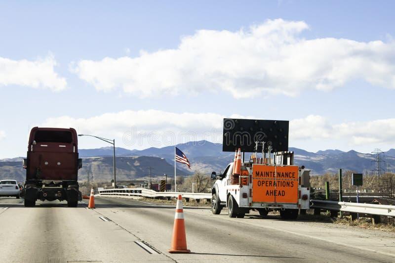 Wegbemanning die aan een bezige snelweg werken stock fotografie