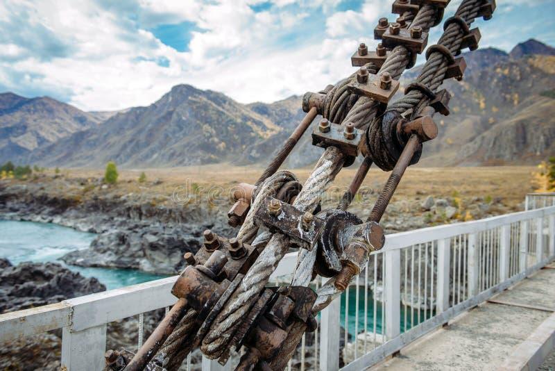 Wegbrug over de rivier in de bergen, het close-up van de metaalstructuur Plaats Gorny Altai, Siberië, Rusland stock fotografie