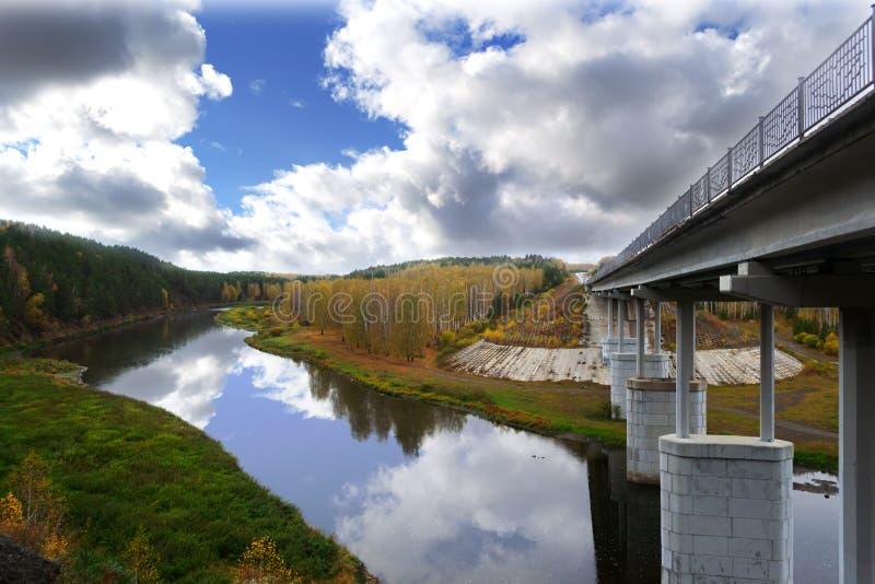 Wegbrug over de rivier met steunen op de achtergrond van de de herfst bos en kleurrijke hemel met wolken stock foto's
