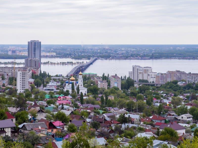 Wegbrug over de Volga rivier tussen de steden van Saratov en Engels De stads` s horizon Een orthodoxe kerk kan stock foto