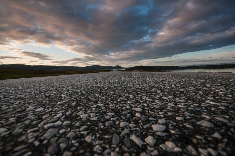 Wegclose-up met bergen in de afstand en een dramatische zonsonderganghemel royalty-vrije stock fotografie