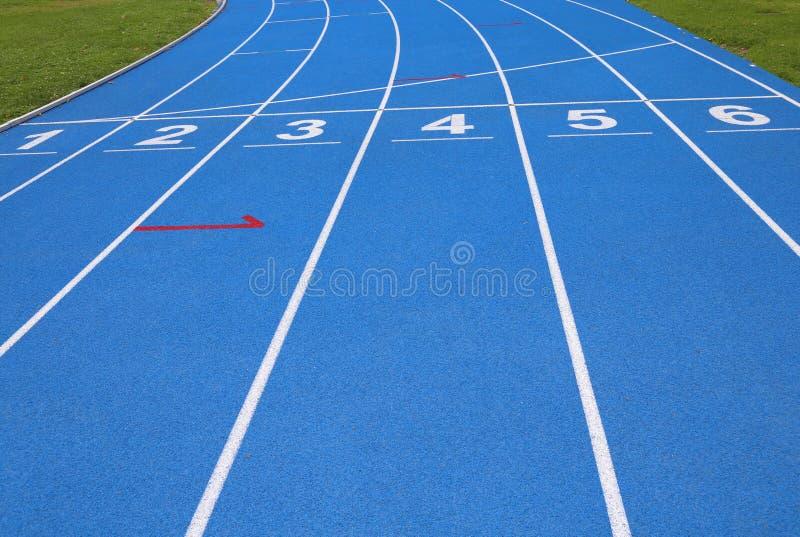 Wege einer blauen athletischen Bahn mit Nr. eine zwei drei vier f stockfotos