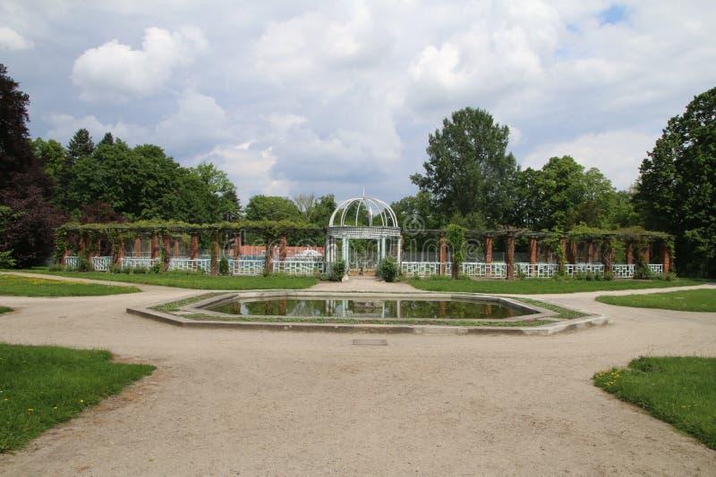 Wegen en fontein in een park met symmetrische architectuur op een bewolkte warme dag stock foto's