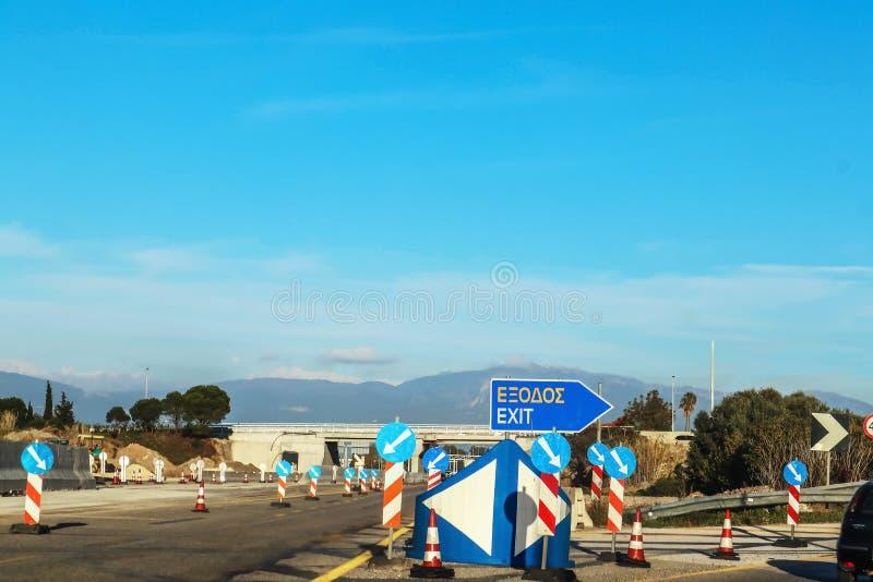 Wegenbouw in Griekenland met een Uitgangsteken in het Grieks en het Engels en veel de tekens van de wegrichting onder een viaduct stock afbeeldingen