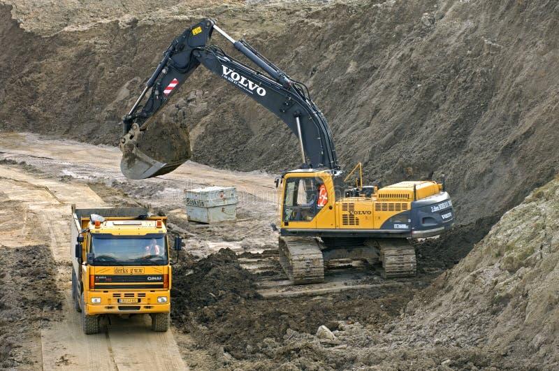 Wegenbouw met vrachtwagen en graafwerktuig stock foto's