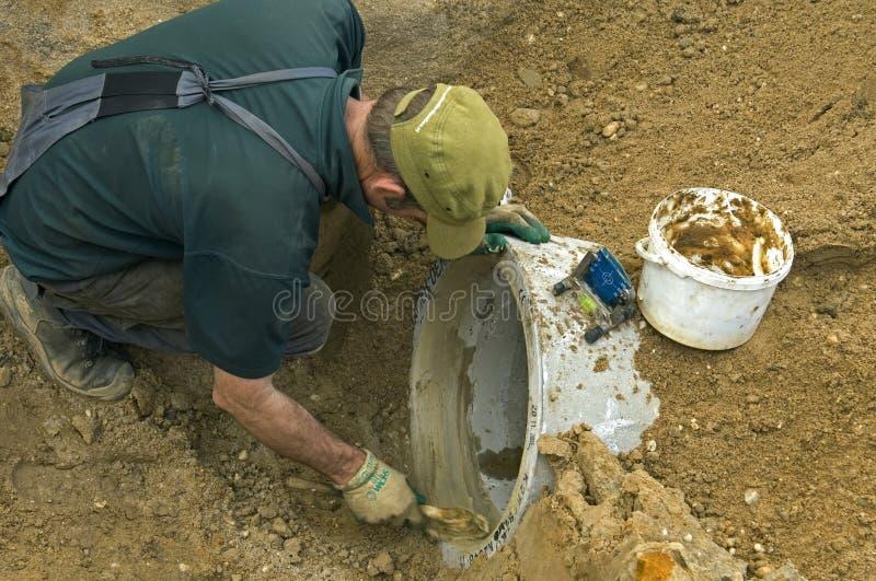 Wegenbouwarbeider die nieuwe rioolpijp leggen royalty-vrije stock foto