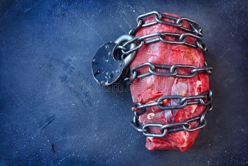 wegetarianizm Weganinu karmowy pojęcie z kawałkiem mięso, kruszcowy łańcuch i kędziorek, zdjęcie stock