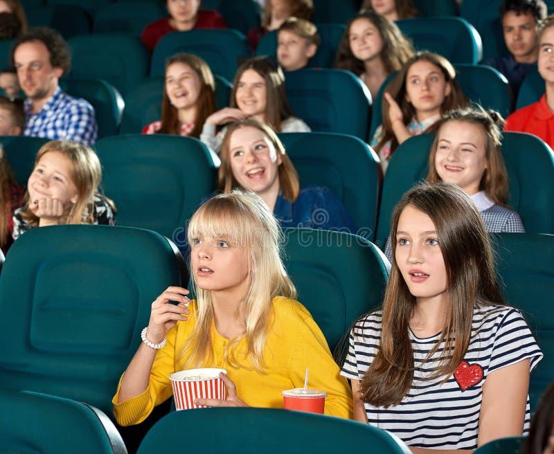 Weggegaane meisjes die op film in de bioskoopzaal letten stock afbeelding