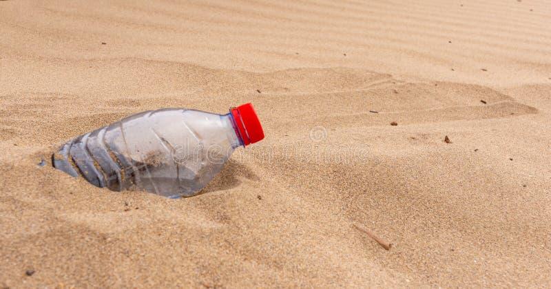 Weggeworfene Plastikwasserflaschenhälfte begraben auf einem Strand im Sand stockfoto