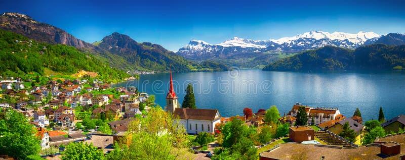 By Weggis och sjö Lucerne som omges av schweiziska fjällängar fotografering för bildbyråer