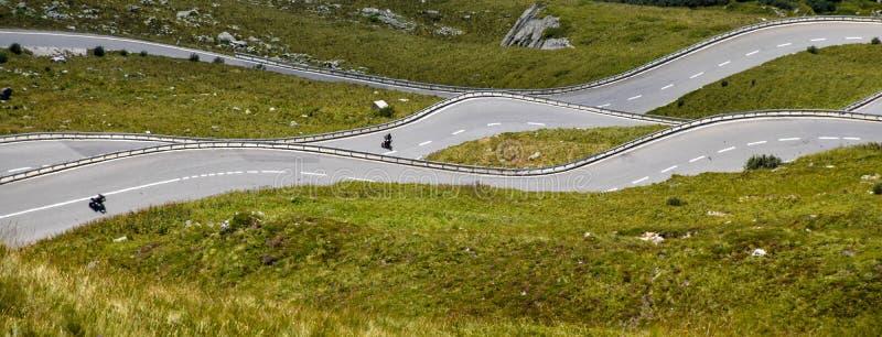 Wegkrommen zoals golven in de groene heuvels van de Zwitserse Alpen royalty-vrije stock afbeelding