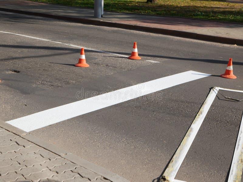 Wegmarkering Een wegmarkering tekenen besproeien in de wegenbouw De werknemer trekt een witte lijn op het oppervlak van de straat stock foto
