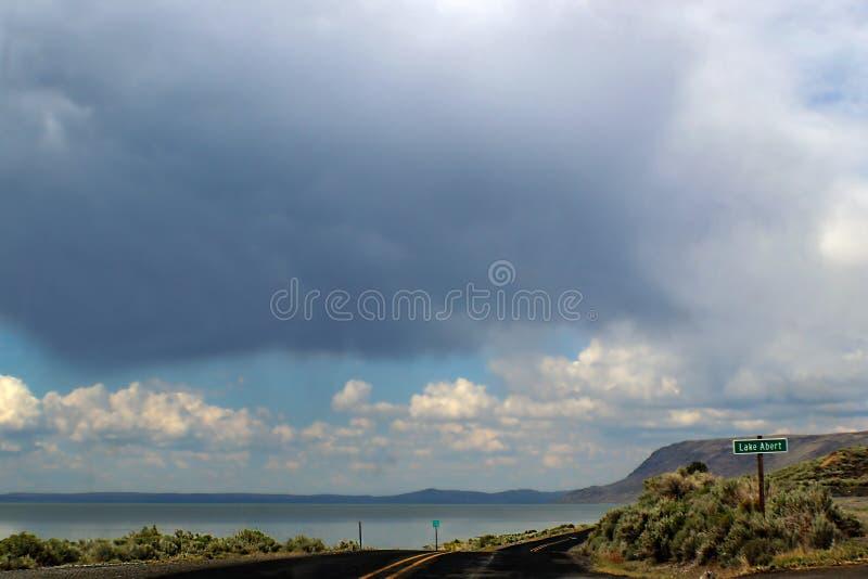 Wegreis - Blacktop twee krommen van de steegweg langs Meer Abert in Oregon naar mountians met dramatische stormysky overheadkoste royalty-vrije stock foto