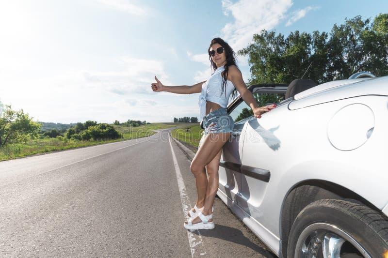 Wegscène: sexy donkerbruin meisje die zich dichtbij hun gebroken auto en lift bevinden Achter mening Ran Out van Gas Problemen me royalty-vrije stock foto's